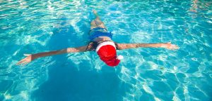 Back view of beautiful woman in santa hat on blue water image