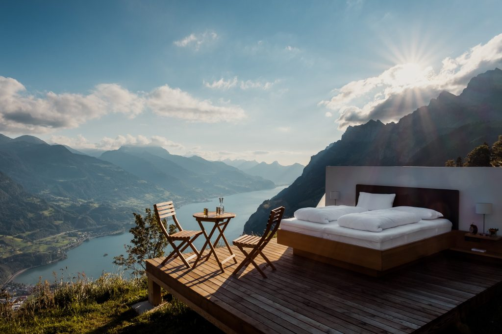 Picture of a big bed on a porch with an open landscape background showing water and mountains
